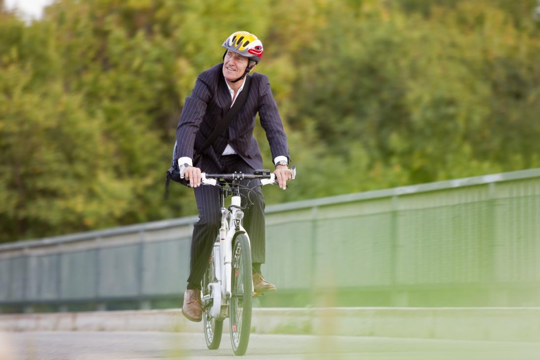 [homem sênior comutar para trabalhar em uma bicicleta]