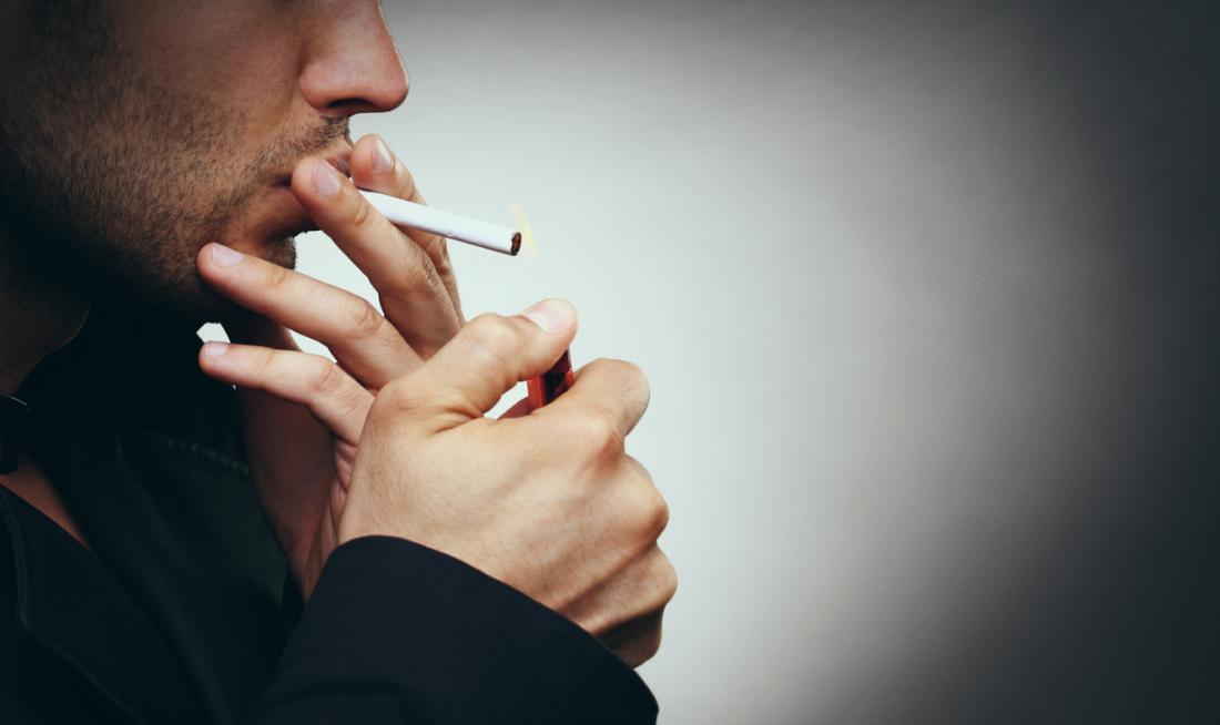 Mann, der eine Zigarette in einem verdunkelten Raum raucht
