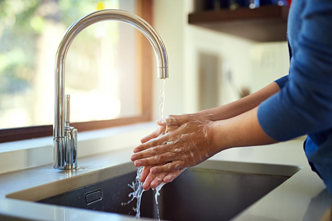 Person, die ihre Hände in der Wanne unter fließendem Leitungswasser wäscht.