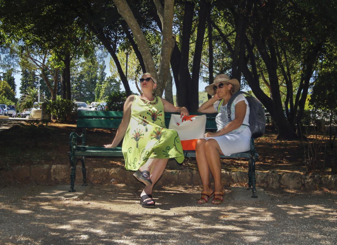 due donne sedute su una panchina all'ombra