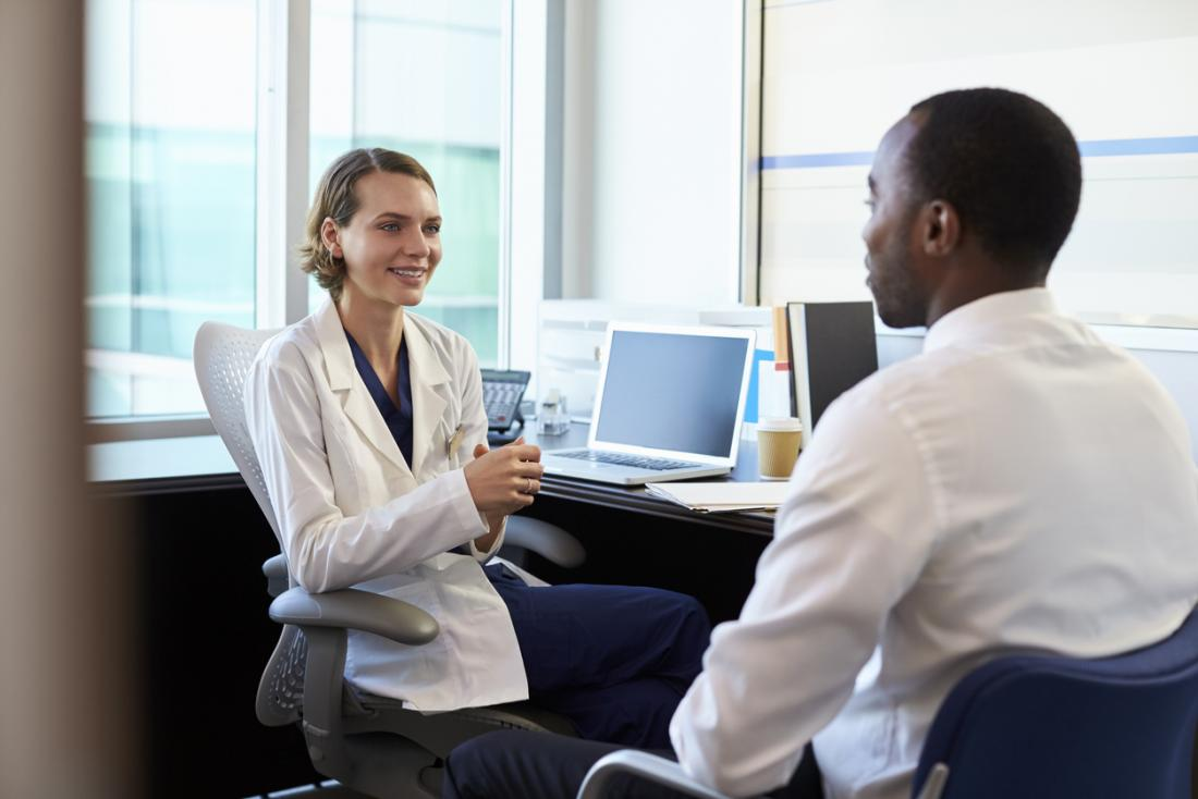 Paciente masculino novo que fala com o doutor fêmea em seu escritório.