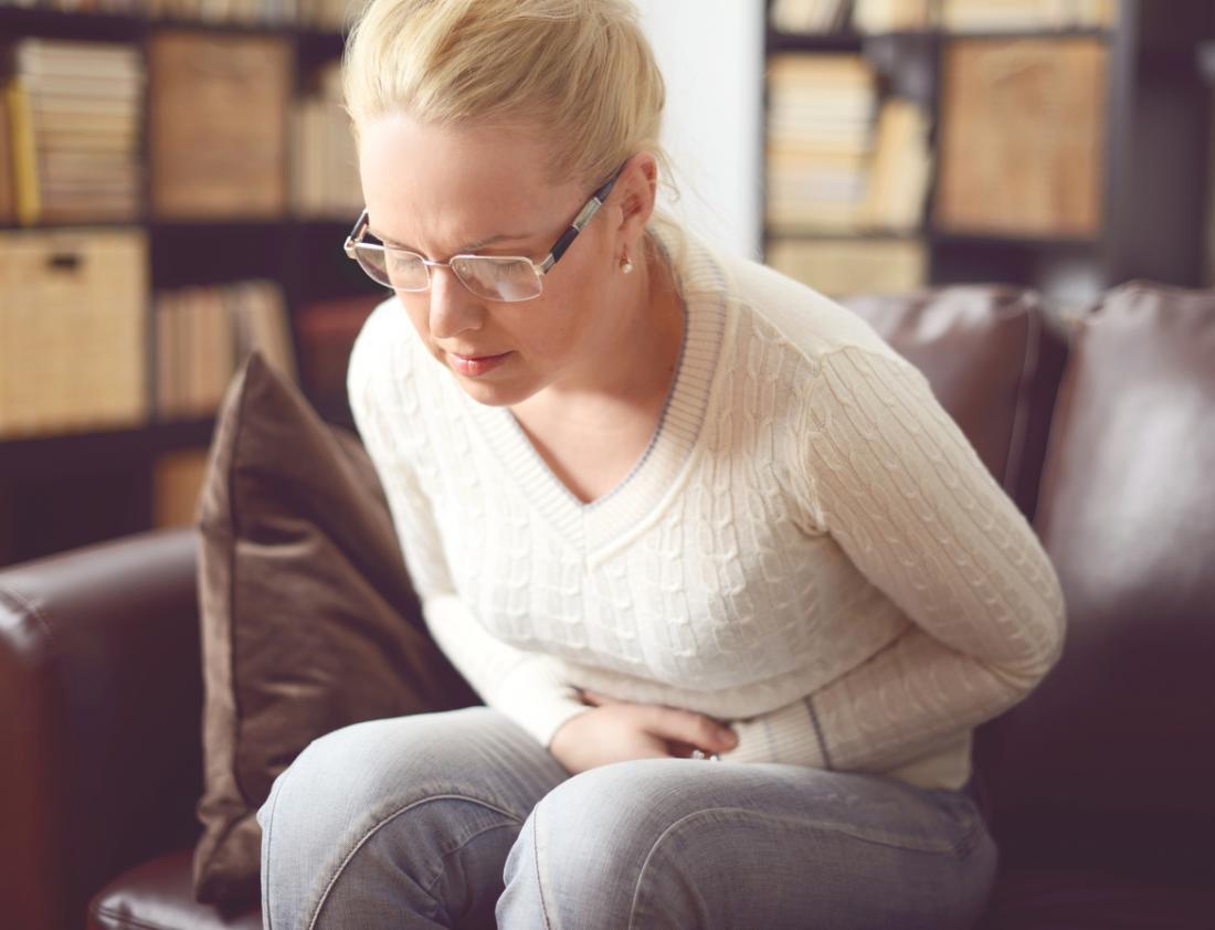 Femme assise, tenant le ventre dans la douleur