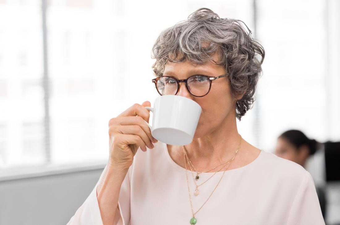 [mulher bebendo chá cohosh preto para a menopausa]