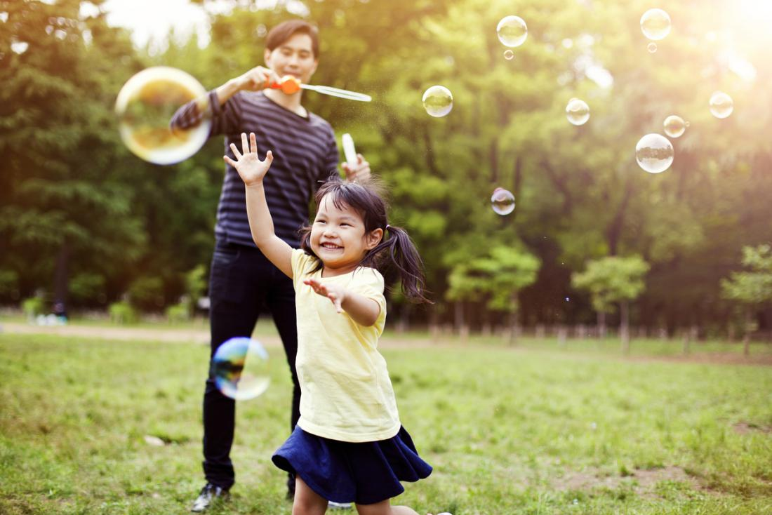 泡で遊んでいる外の父と子供