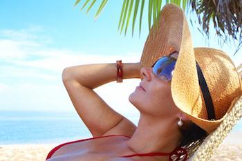 Dame, die auf einem tropischen Strand im Schatten einer Palme stillsteht und Hut und Sonnenbrille trägt