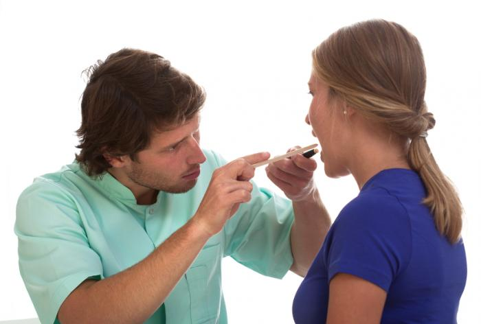 [Doutor examinando a boca do paciente]
