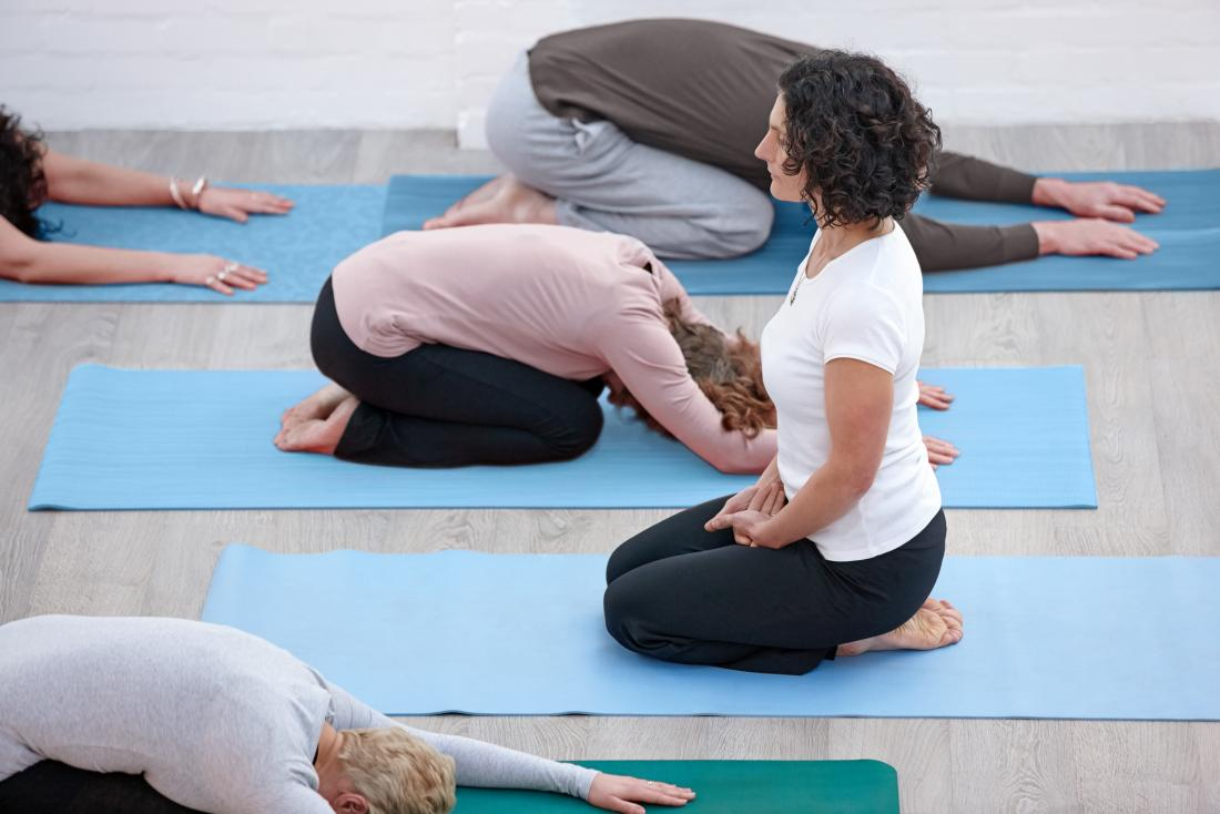 istruttore femminile con studenti che praticano yoga