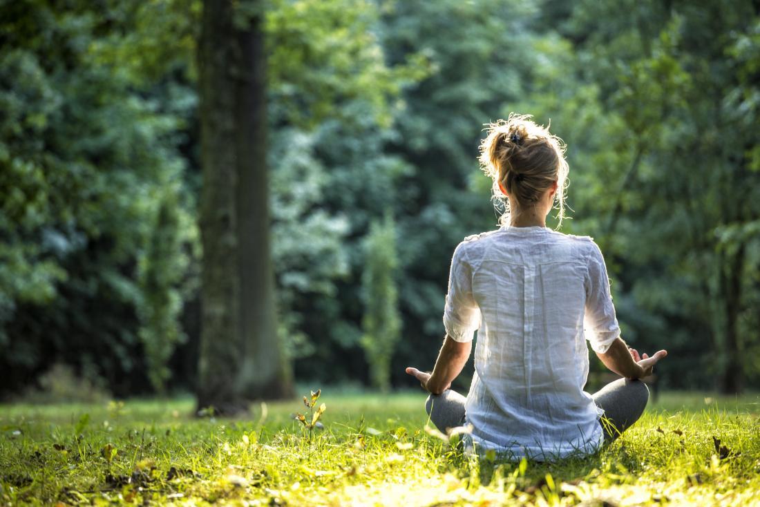 心臓の動悸を止める方法かもしれない森で瞑想している女性