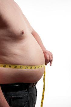 彼の腰を測定する肥満男性