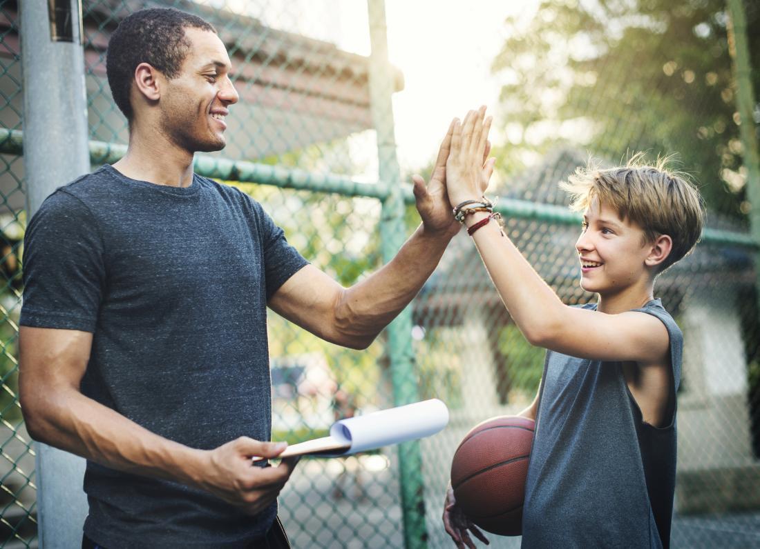 jeune garçon highfiving professeur de basket-ball