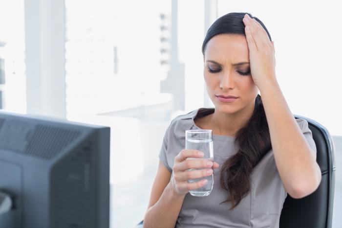 Una donna con un mal di testa beve un po 'd'acqua.