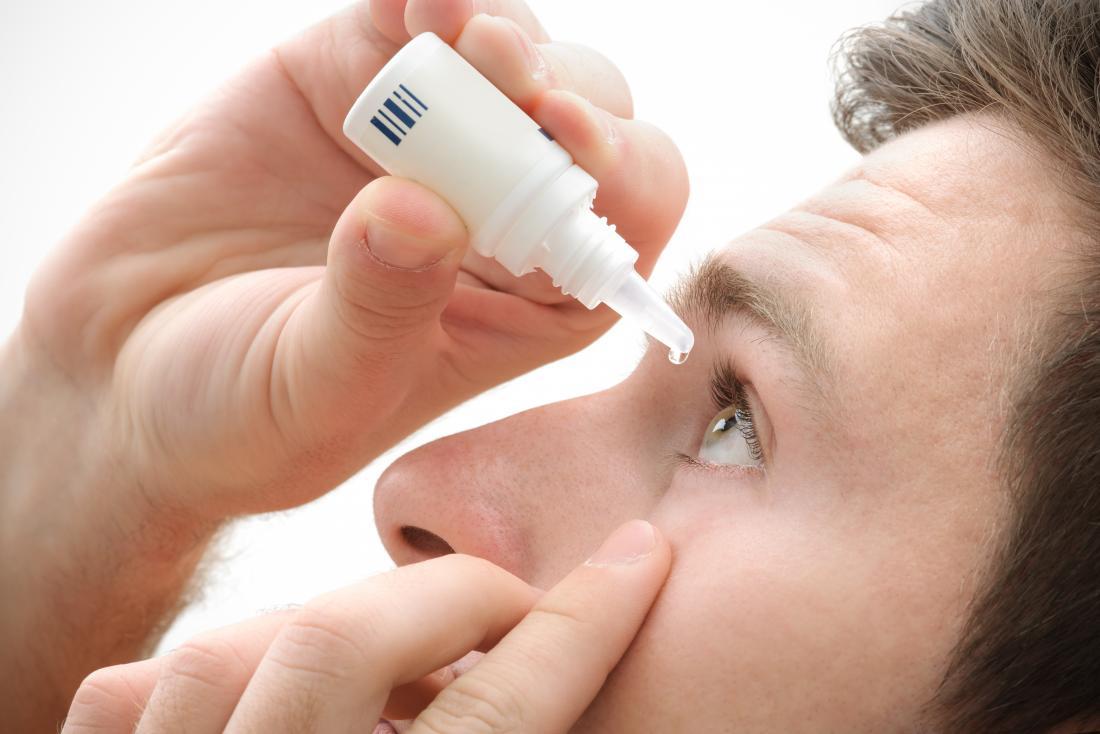 Uomo che utilizza gocce d'occhio saline per combattere le reazioni allergiche.