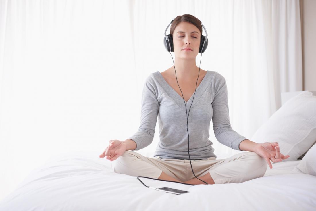 Frau, die das Kreuz mit Beinen besetzt in der Lotosyogaposition sitzt und meditiert beim Hören auf Kopfhörer.