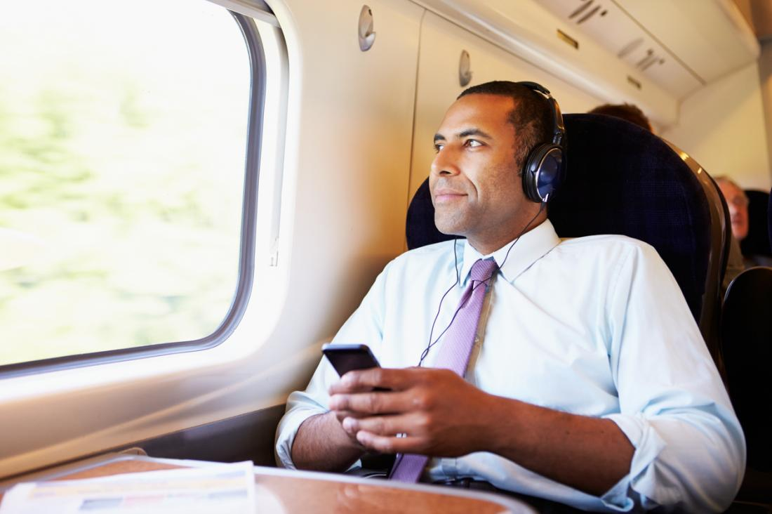 ビジネスマン、電車で、音楽を聴いて、彼がリラックスして外を見る。