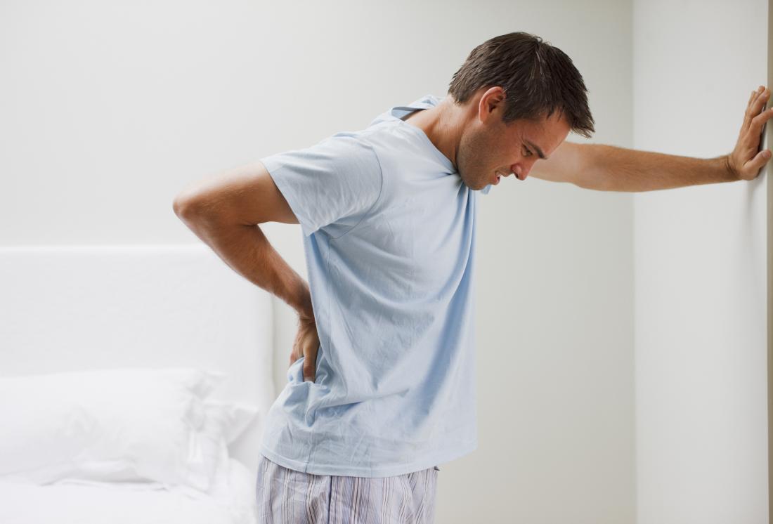 Homme tenant son dos dans la douleur, appuyé contre le mur.