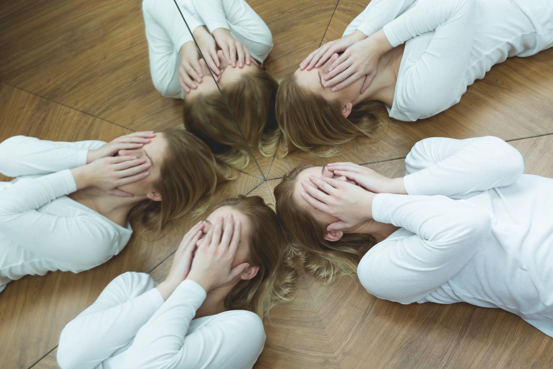 Femme émotive avec un trouble de l'humeur ou de la personnalité, allongée à côté des miroirs avec les mains couvrant son visage.