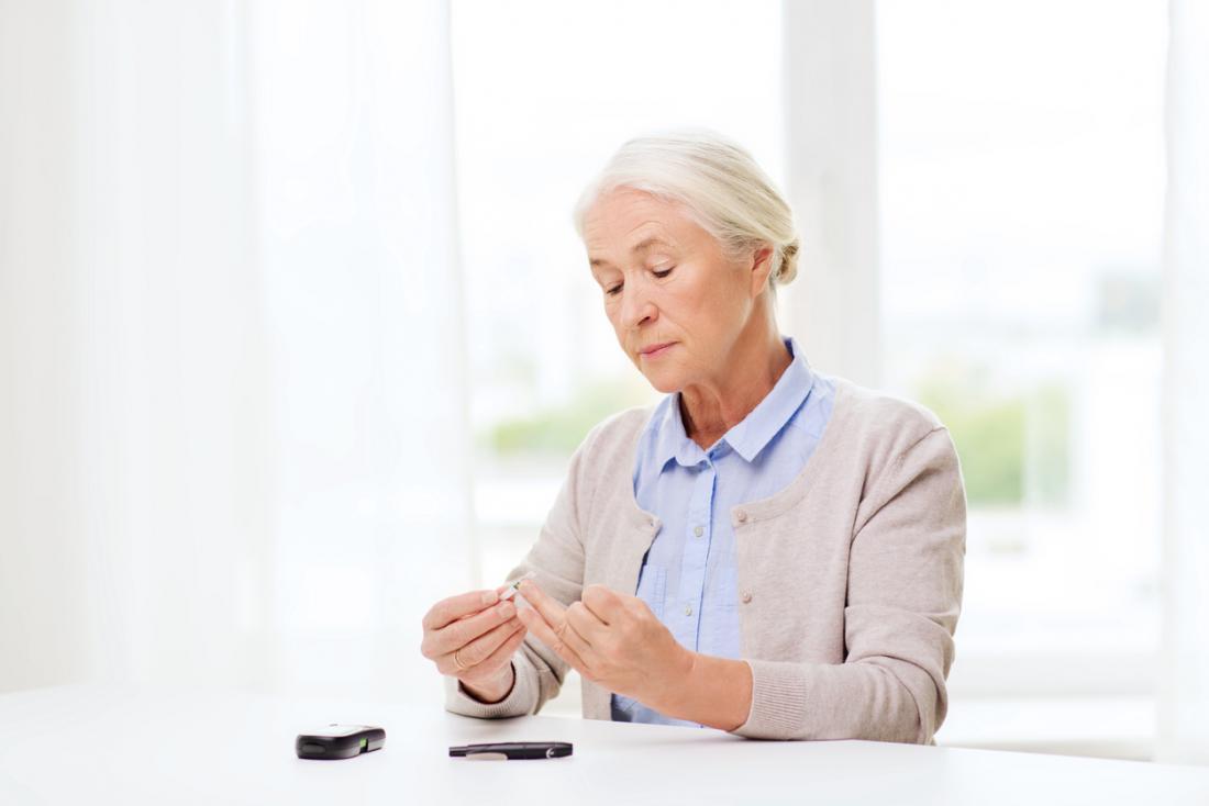 [Femme plus âgée vérifiant son niveau de glucose dans le sang]