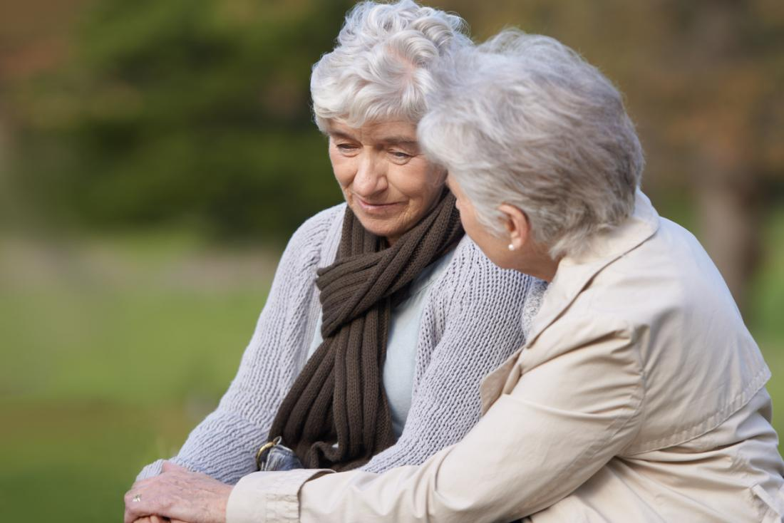 [Femme plus âgée réconfortant son amie sur un banc]