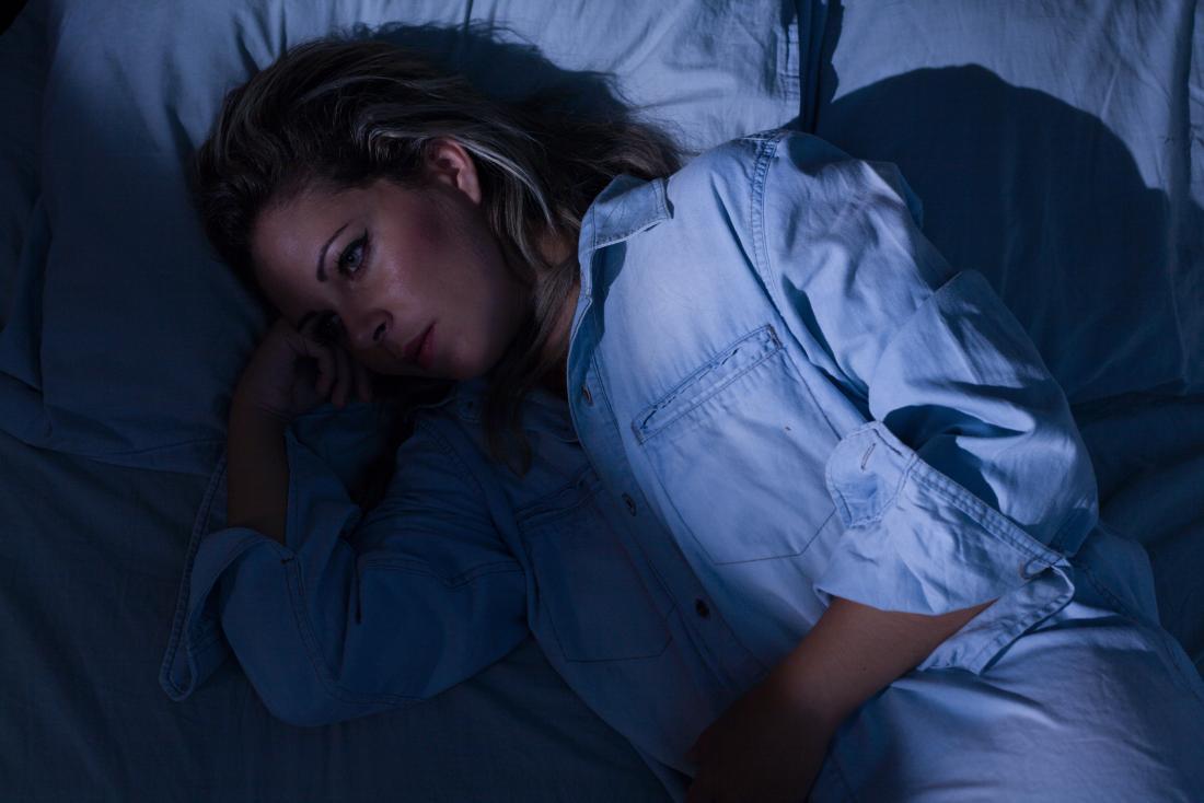 Femme couchée dans son lit les yeux ouverts souffrant d'hallucinations hypnagogiques