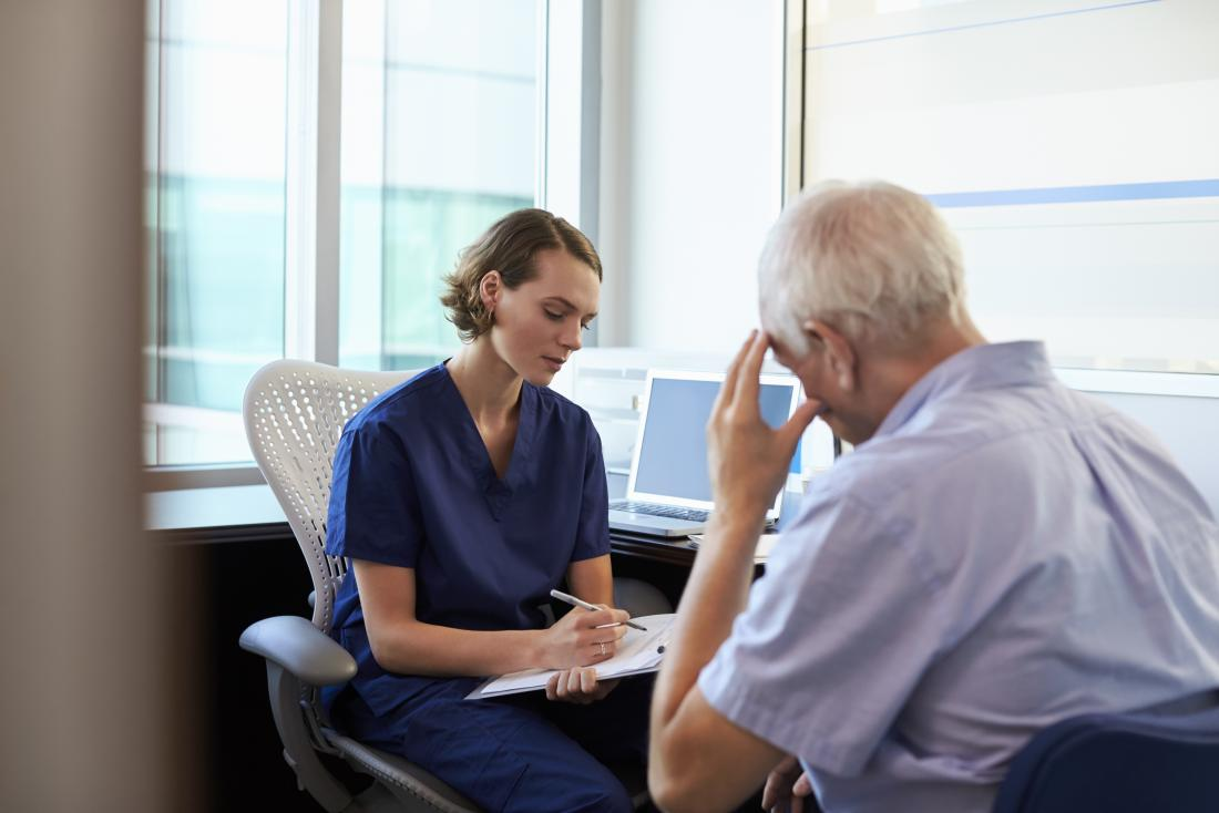 GP écoutant un patient masculin déprimé et prenant des notes