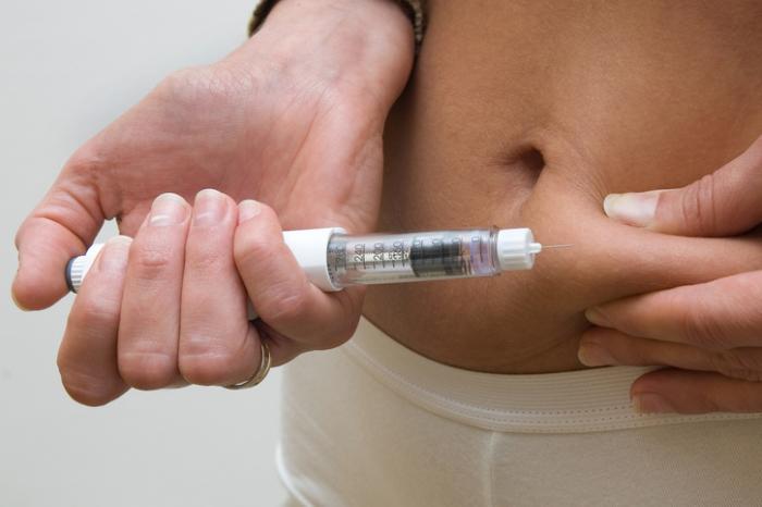 Dame injectant de l'insuline dans le ventre
