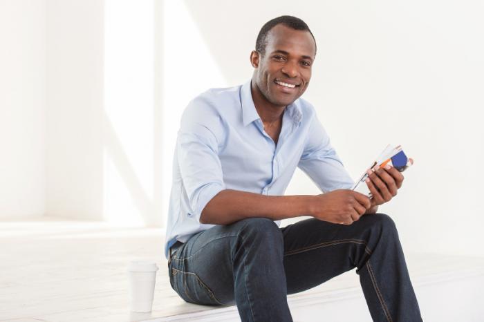 Un uomo sta sorridendo e sedendosi.