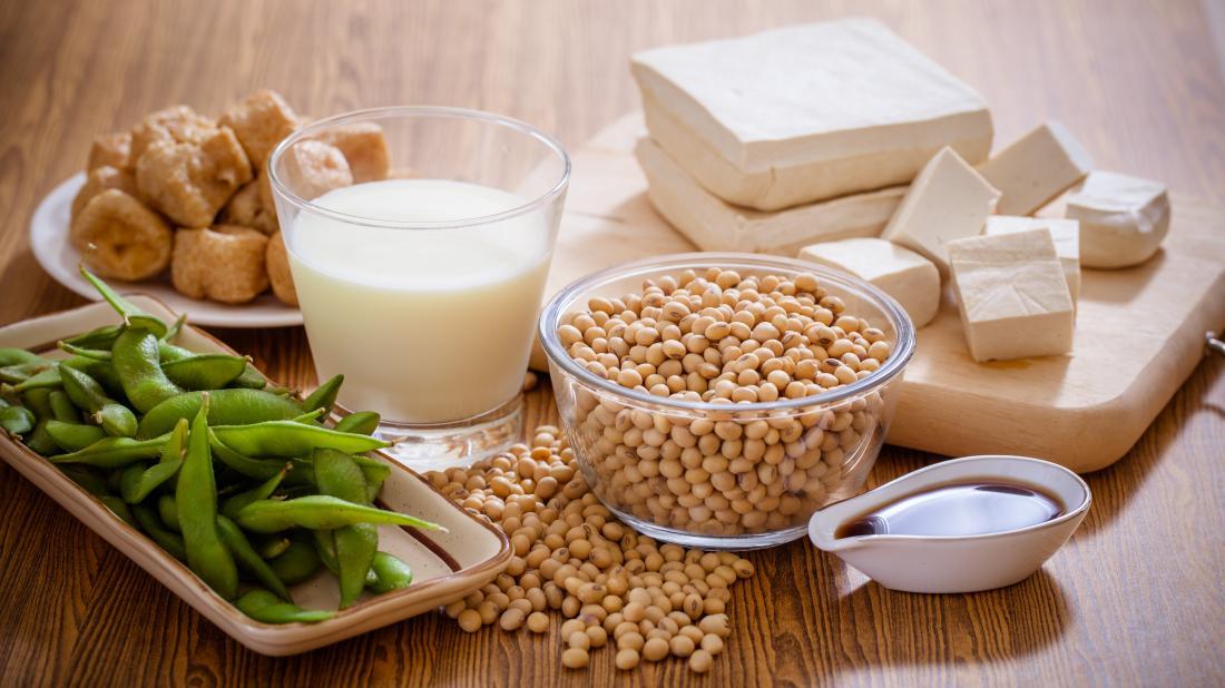 大豆、豆腐、醤油、およびテンペを含むテーブルに並べられた大豆食品。