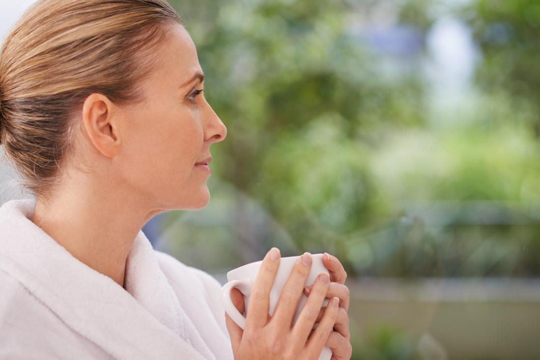 Vor-Wechseljahrfrau im Bademantel Tee oder Kaffee trinkend und Garten untersuchend.
