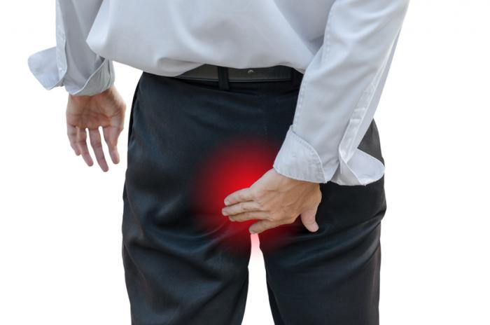 Um homem com hemorróidas toca seu ânus.