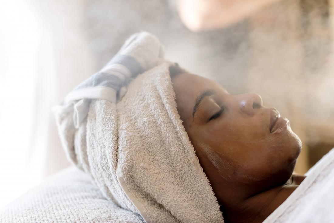 Donna che riceve un trattamento termale con terapia a vapore per migliorare la pelle del viso.