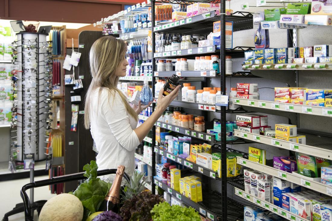スーパーマーケットでビタミンやサプリメントを買う女性、さまざまなブランドのラベルをチェックする女性