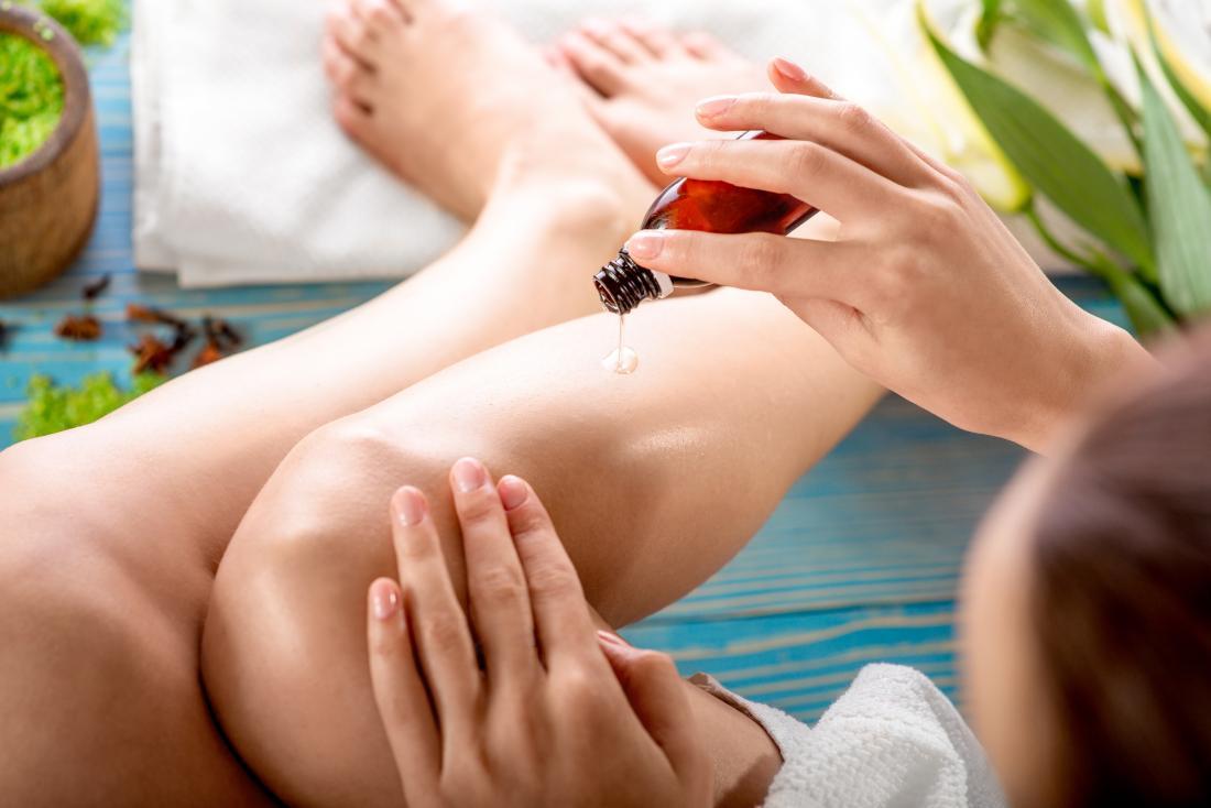 女性は脚の上の皮膚にエッセンシャルオイルを塗布して潤いを与えます。