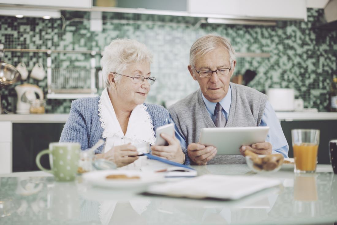 [Couple de personnes âgées prenant son petit déjeuner avec téléphone et tablette]