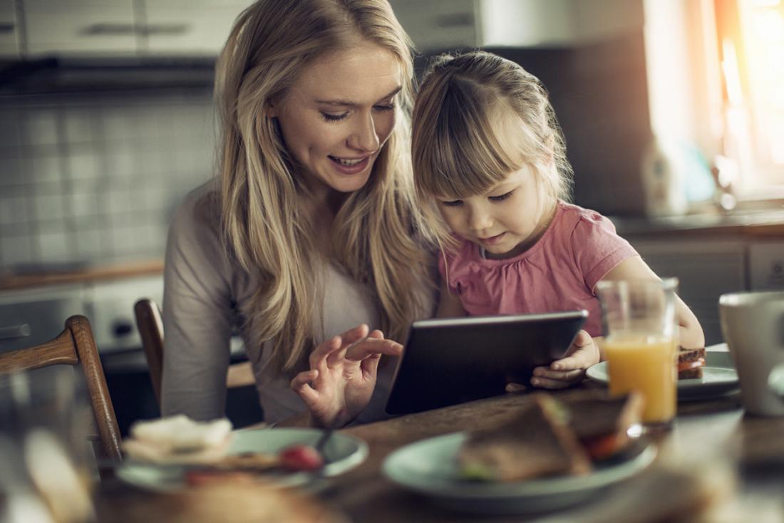 [Maman et enfant regardant une tablette en mangeant le petit déjeuner]