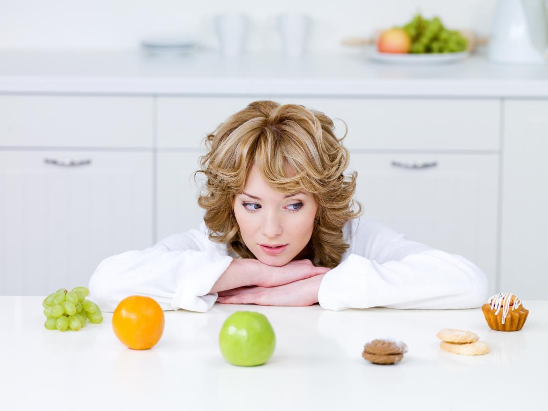 jeune femme essayant de choisir entre les fruits et les gâteaux