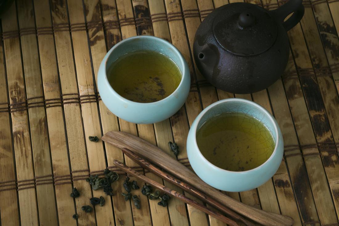 panela e xícaras de chá verde