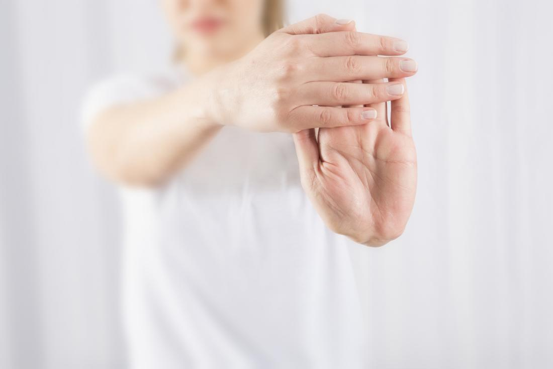 La persona che tira indietro il polso come esercizio per il dolore all'avambraccio