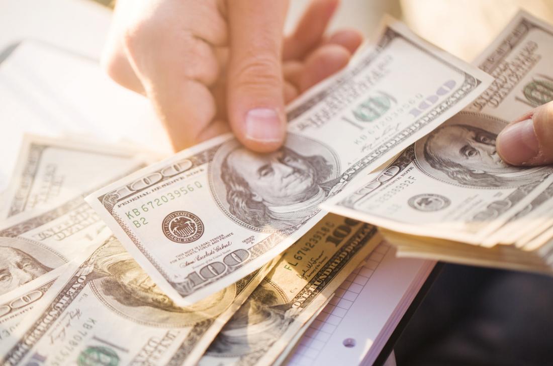 Pessoa contando dinheiro para procedimento médico.