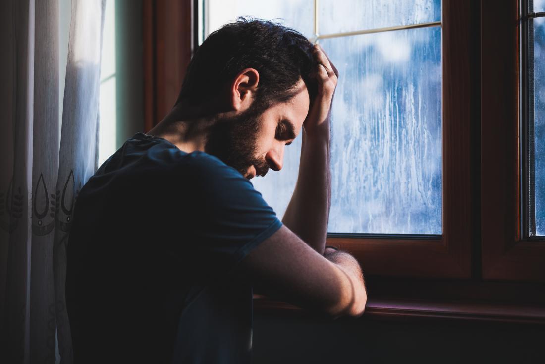 悲しい、そして夢中に見える、頭を持っている窓の男。