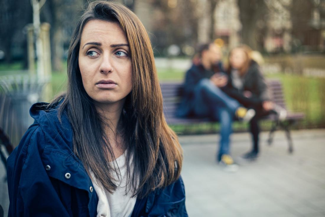 背中の友達が一緒に座っている間に彼女自身の上に座っている悲しい女性。