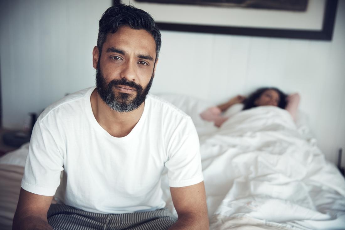 Người đàn ông với tuyến tiền liệt mở rộng tự hỏi làm thế nào nó sẽ ảnh hưởng đến cuộc sống tình dục của mình ngồi trên giường trong khi người phụ nữ ngủ.