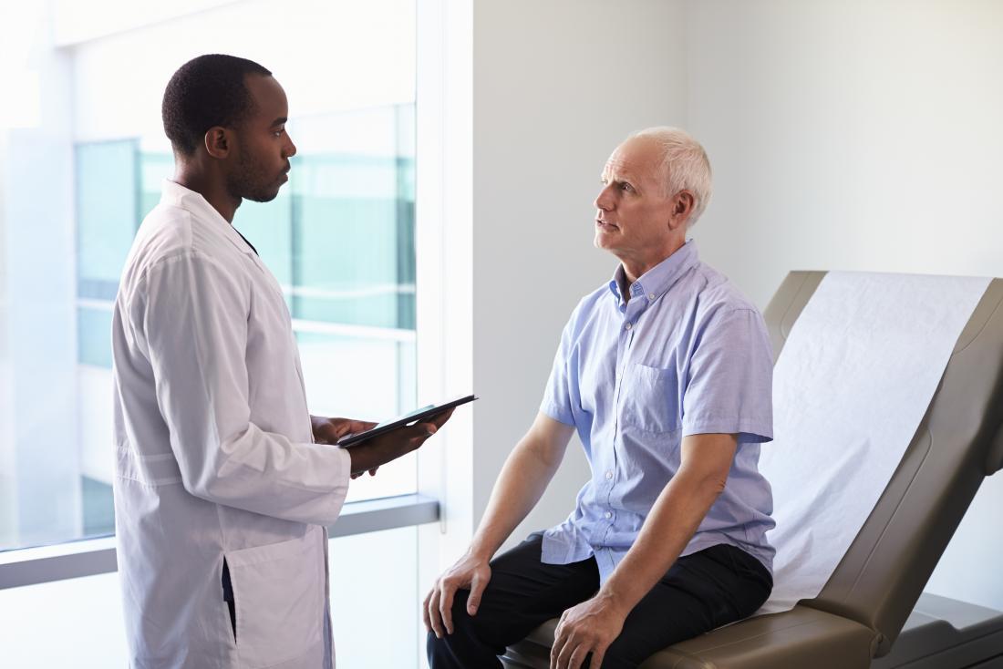 Người đàn ông trưởng thành ngồi trên bàn khám trong khi bác sĩ nói với anh ta.