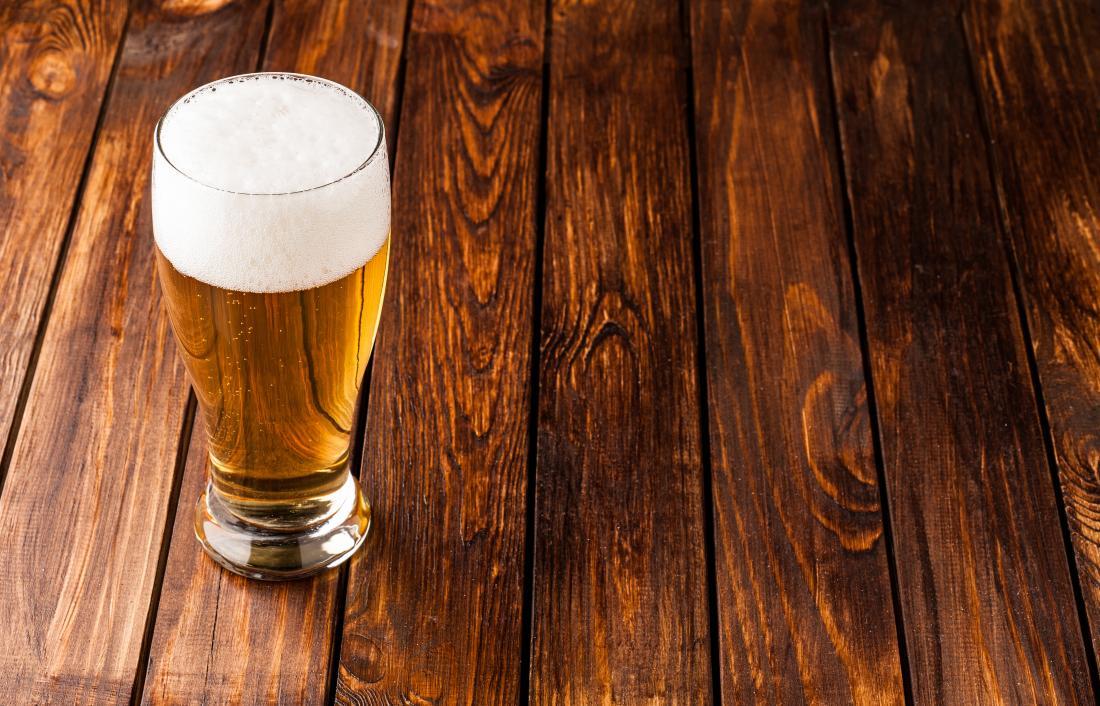 Bia trong ly trên bàn gỗ.