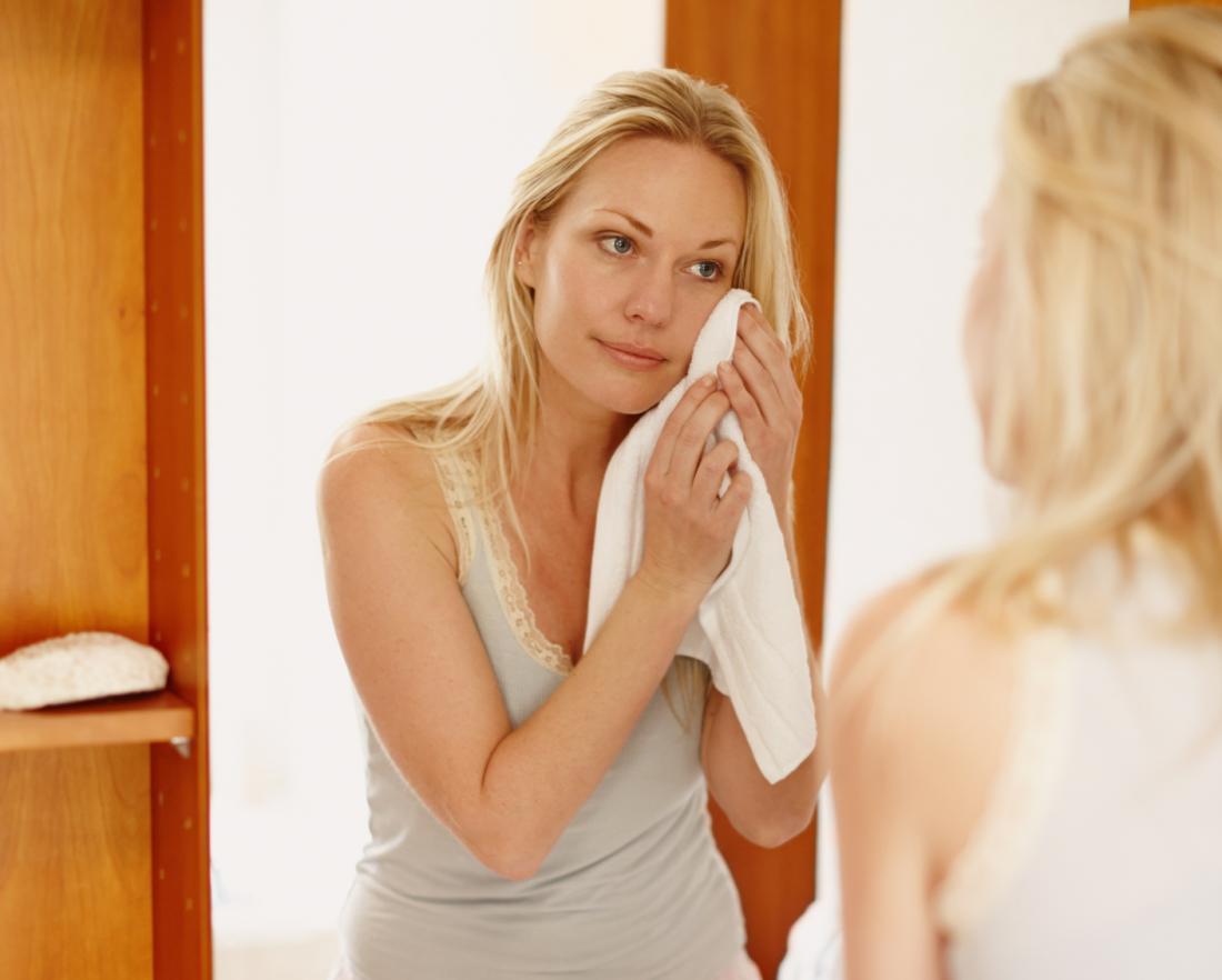 femme tenant un gant de toilette pour faire face