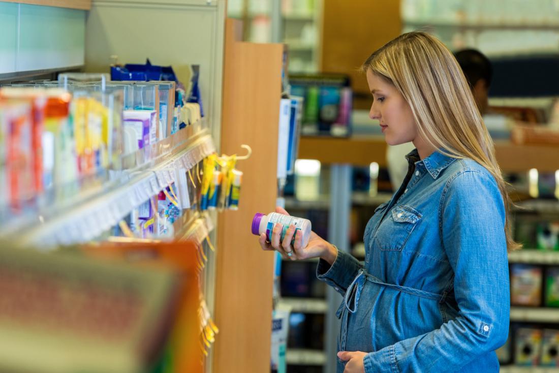 Hamile kadın dükkanda ek etiket arkasında bilgi okuma.