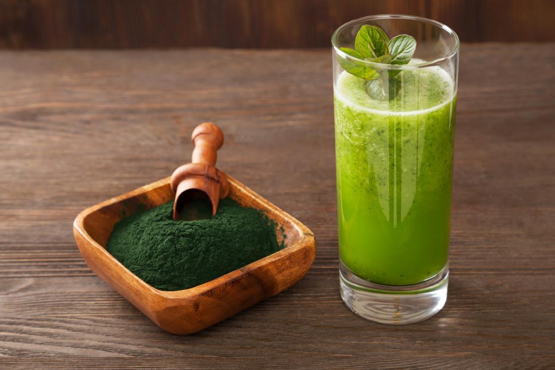 Pó verde do chlorella em uma bacia de madeira, ao lado de um vidro com uma bebida verde do smoothie.