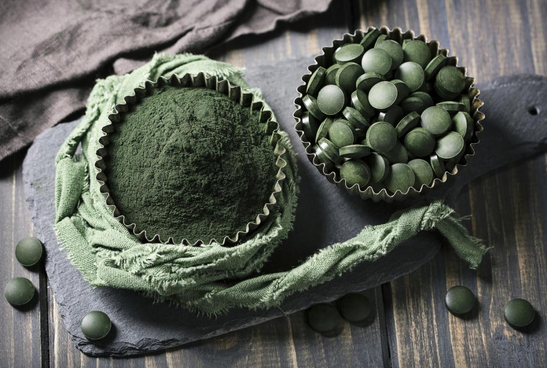 Suplementos de chlorella verde e pó em tigelas separadas.