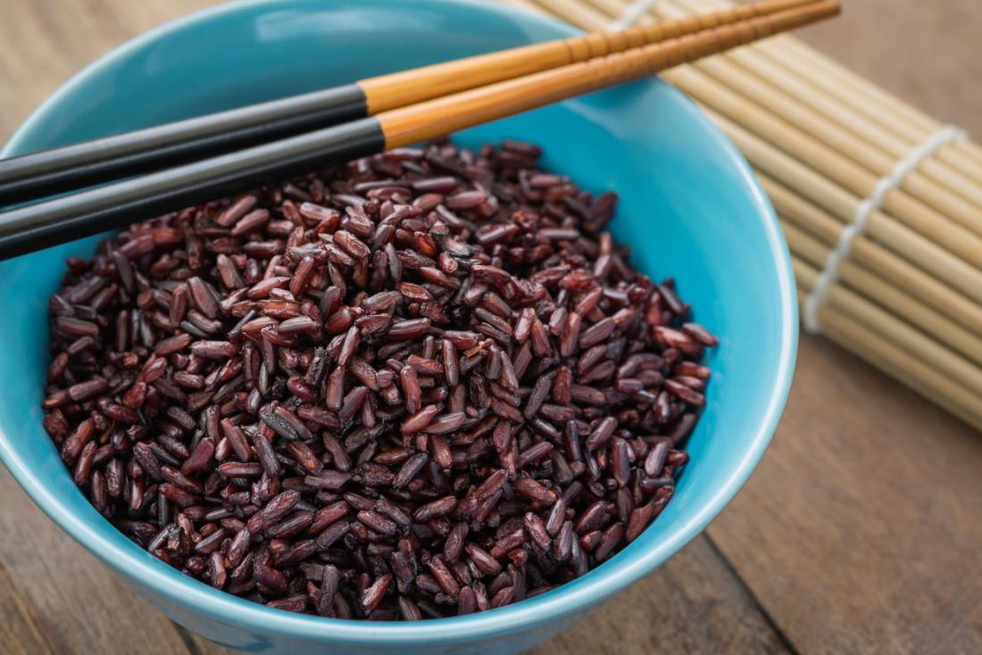 Arroz roxo e preto cozinhado em uma bacia com chopsticks.