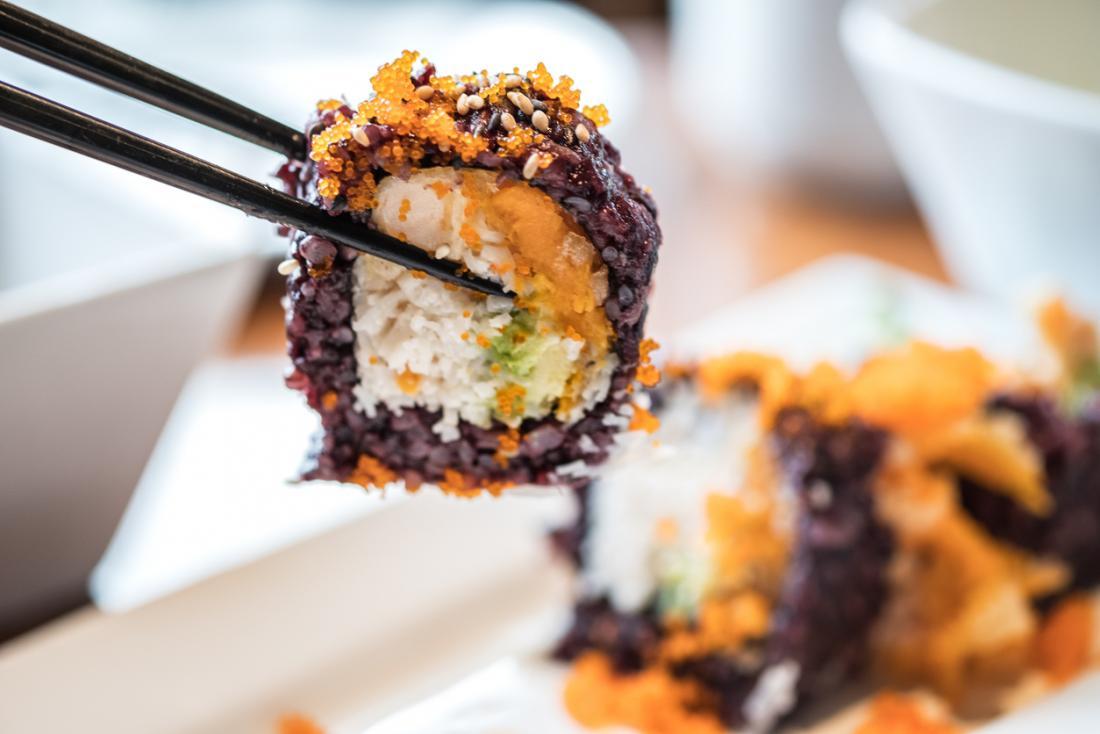 Sushi roll usando arroz branco, preto e roxo, sendo realizada por pauzinhos.