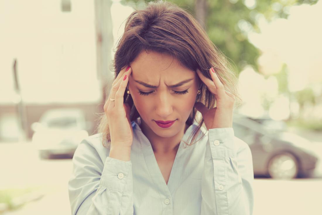Mulher com vertigem esfregando seus templos e franzindo a testa por causa da dor de cabeça, do lado de fora.